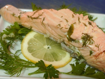 poached salmon on a bed of dill, parsley and lemon