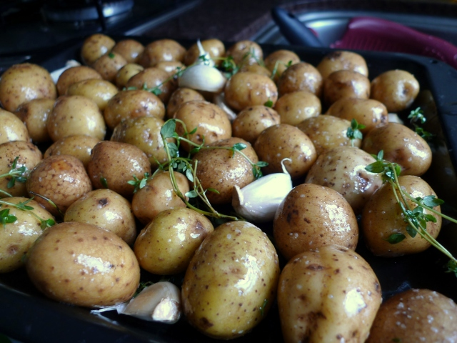 spread potatoes in a pan to roast