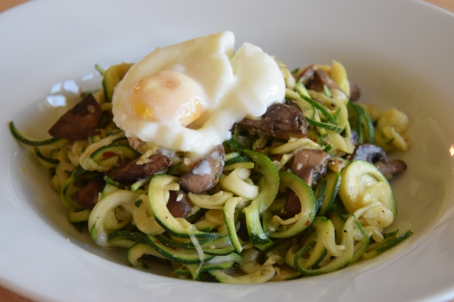 zucchini aglio e olio topped with a poached egg